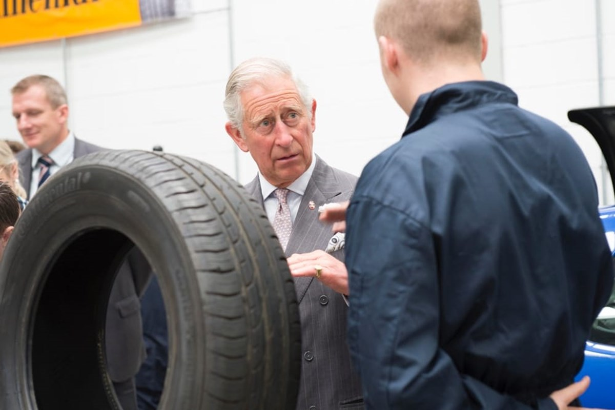 Prince Charles speaking to an apprentice next to car tyre