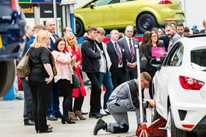 A group at a GTG open day watching and apprentice work on a car in the workshop
