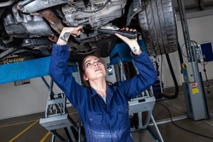 Female apprentice working underneath a car on the ramps