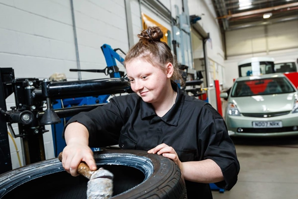 female apprentice checking a tyre